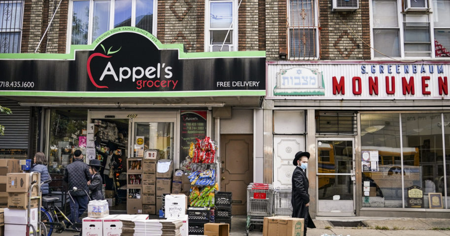 Orthodox Jews pass a grocery store in the Borough Park neighborhood of the Brooklyn borough of New York on Oct. 8, 2020.