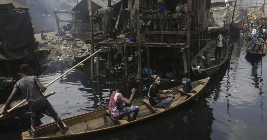 In this March 21, 2020, file photo, people travel by canoe during a coronavirus lockdown in the floating slum of Makoko in Lagos, Nigeria.