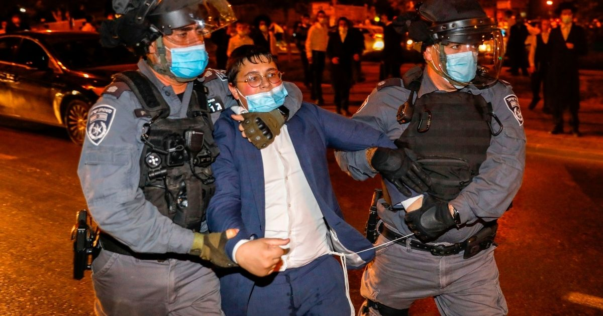 Israeli security forces arrest an ultra-Orthodox Jewish man during a protest against coronavirus restrictions in Jerusalem on Oct. 5, 2020.