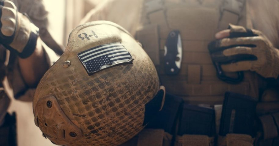 A soldier carries his helmet in the above stock image.