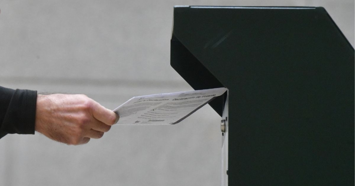 A man deposits his mail-in ballot in a drop box on Oct. 27, 2020, in Philadelphia.