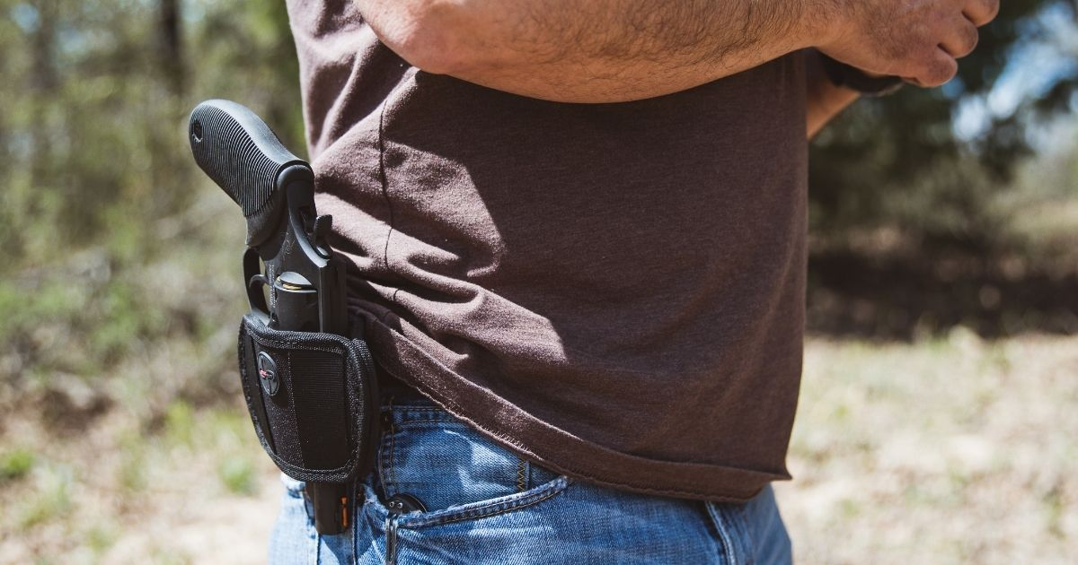 A man carries a gun in a holster in the above stock image.
