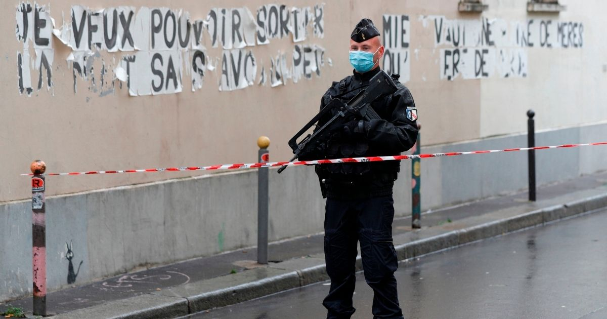 A French police officer blocks the road leading to the scene of an attack in which two people were injured near the former offices of the French satirical magazine Charlie Hebdo by a knife-wielding attacker in Paris on Sept. 25, 2020.