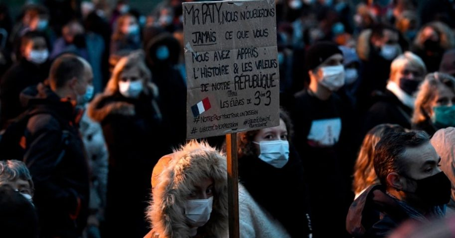 A woman holds a sign reading 'Mr. Paty, we will never forget what you taught us: history and the values of the Republic' during a march on Oct. 20, 2020, in Conflans-Sainte-Honorine, northwest of Paris, after a teacher was beheaded for showing pupils cartoons of Muhammad.
