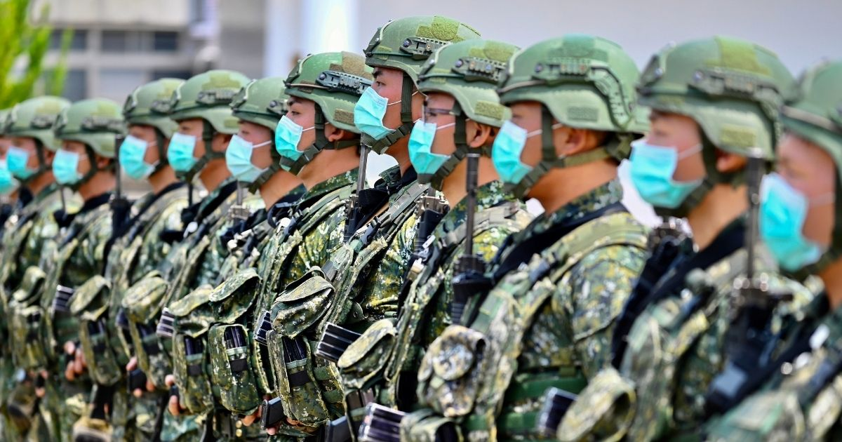 Soldiers wearing face masks listen to an address by Taiwanese President Tsai Ing-wen during her visit to a military base in Tainan, southern Taiwan, on April 9, 2020.
