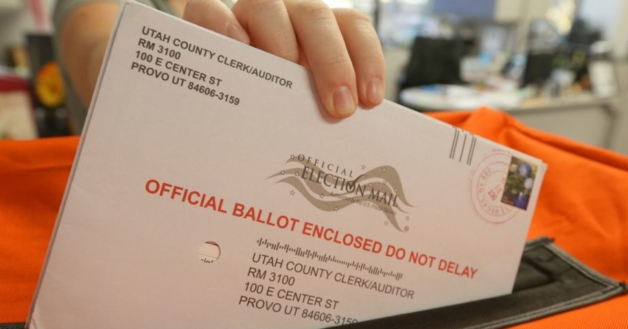 An employee puts a mail-in ballot into a container to register the vote in the midterm elections on Nov. 6, 2018, in Provo, Utah.