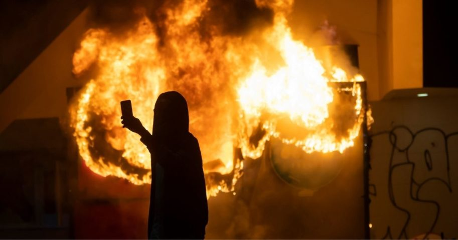 A protester takes a selfie in front of a burning building.