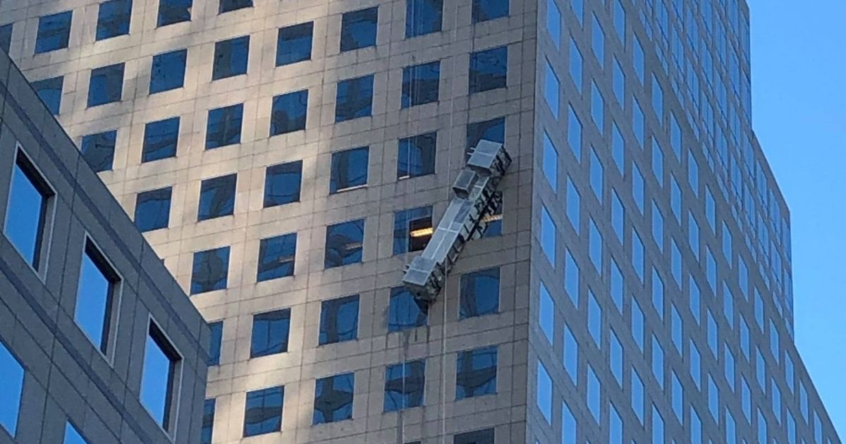 Scaffolding with window washers dangles off a high rise.