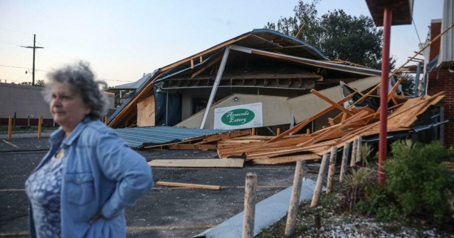 A woman stands in front of a destroyed restaurant after Hurricane Zeta on Oct. 29, 2020, in Chalmette, Louisiana.