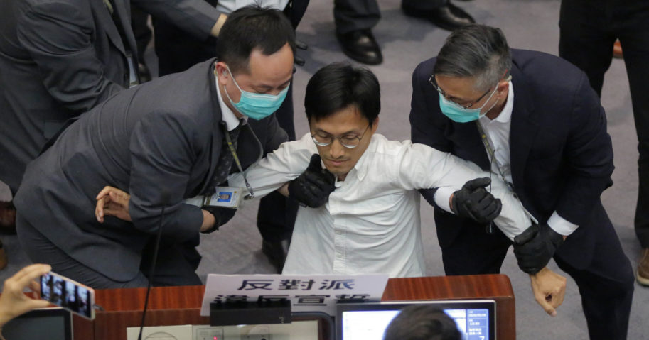 In this May 8, 2020, file photo, pro-democracy lawmaker Eddie Chu is taken away by security guards during a legislative meeting in Hong Kong.