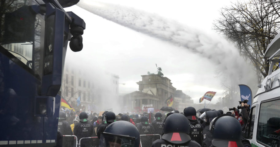 Police use water cannons to move people protesting coronavirus restrictions Wednesday near the Brandenburg Gate in Berlin.