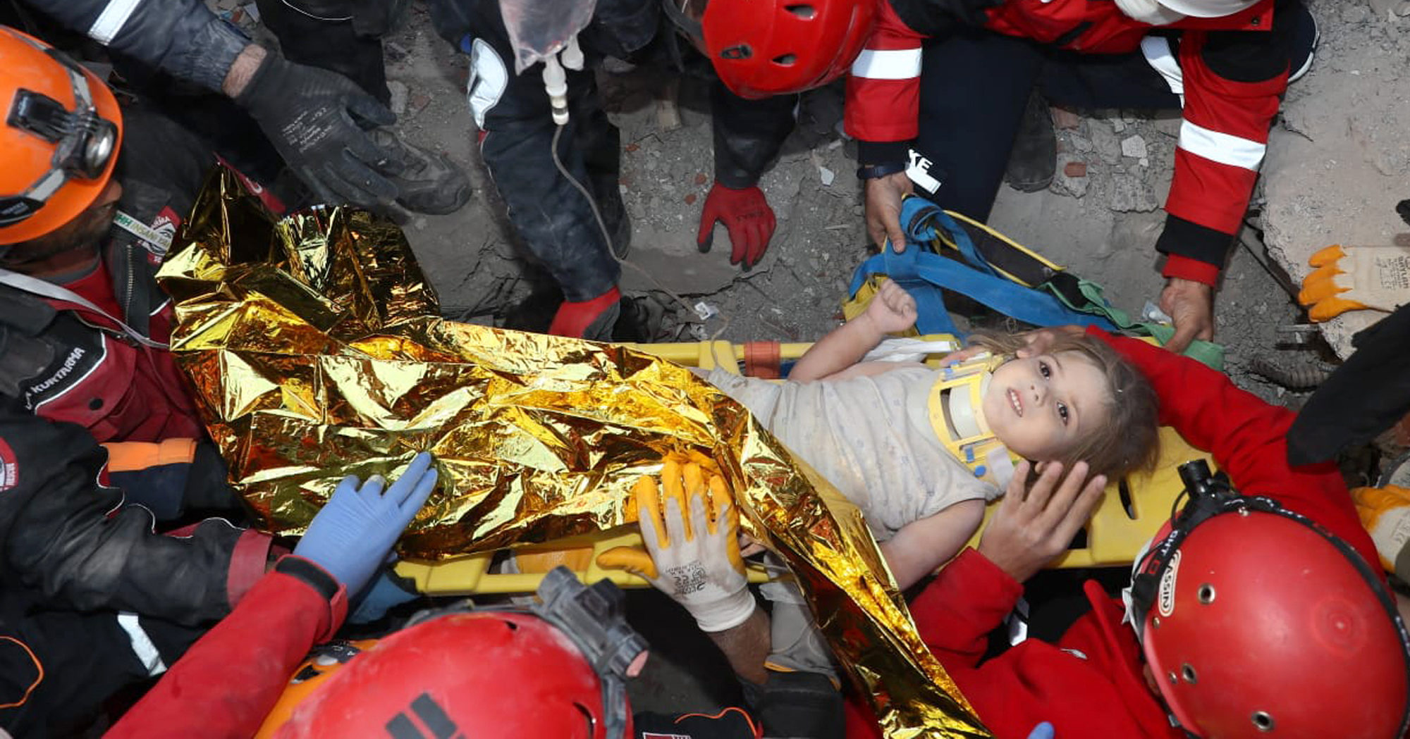 Rescue workers surround Ayda Gezgin in the coastal city of Izmir, Turkey, on Nov. 3, 2020, after pulling her out alive from the rubble of a collapsed apartment building four days after a strong earthquake hit Turkey and Greece.