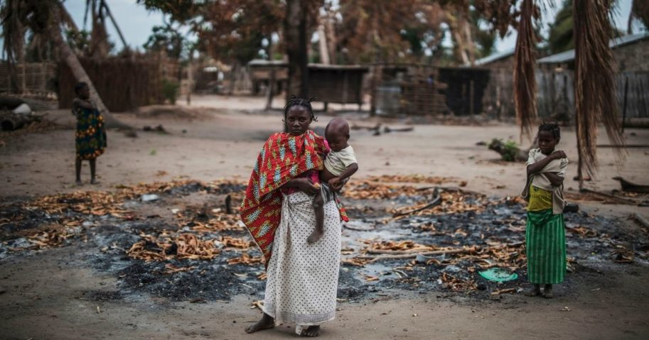 A woman holds her younger child while standing in a burned out area in the village of Aldeia da Paz outside Macomia, on Aug 24, 2019. The village had been attacked earlier that month.