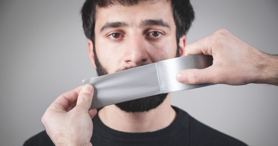 A man has his mouth taped shut in the stock image above.
