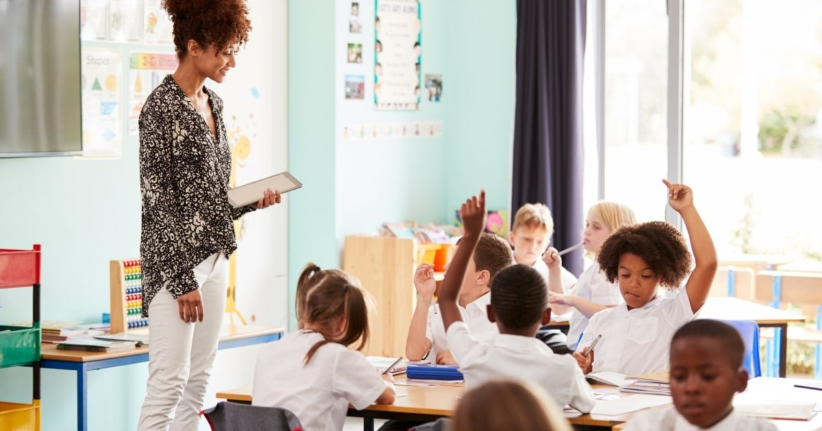 A teacher with her classroom of students is pictured above.