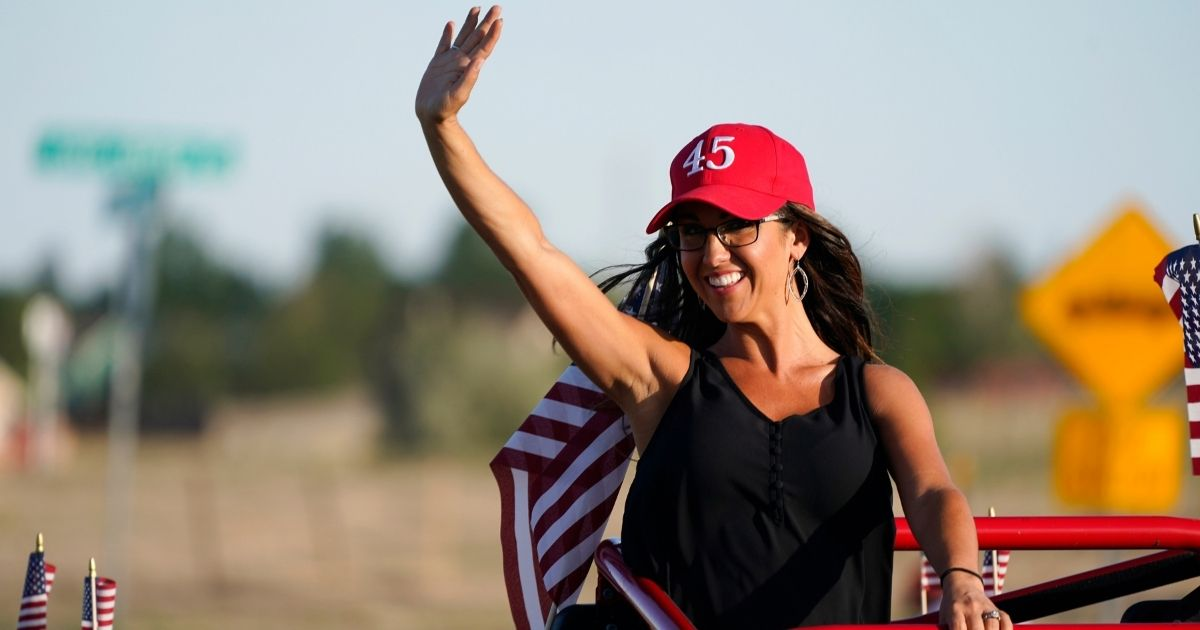 """Republican congressional candidate Lauren Boebert waves during a """"freedom cruise"""" staged by her supporters Sept. 4 in Pueblo West, Colorado."""