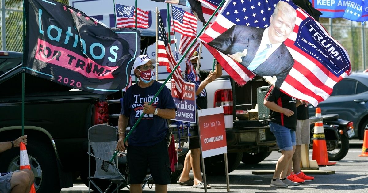 Orlando Bacallao waves a banner with the face of President Donald Trump outside of the early voting location at the John F. Kennedy Library in Hialeah, Florida, on Oct. 27.