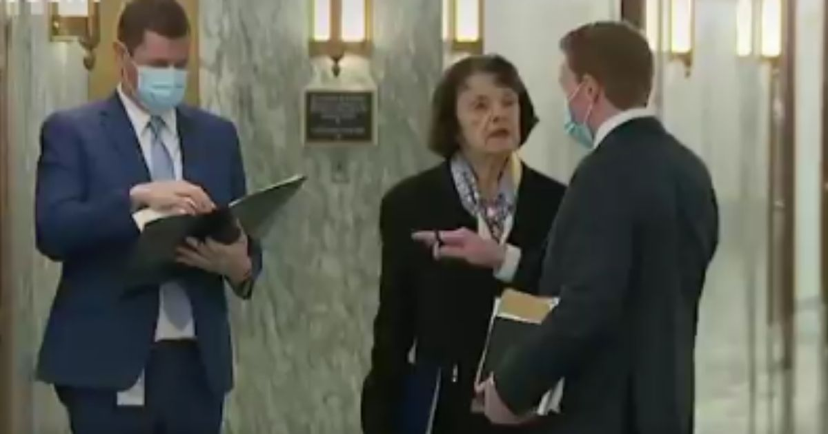 In another glaring example of left-wing hypocrisy, Sen. Dianne Feinstein was caught on video not wearing a mask or social distancing while speaking to what appeared to be an aide in a Capitol Hill hallway.