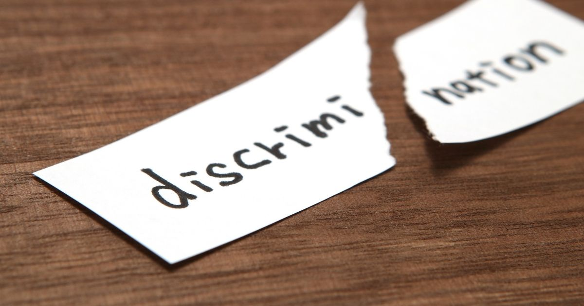"""A scrap of paper with the word """"discrimination"""" is pictured in the stock image above."""