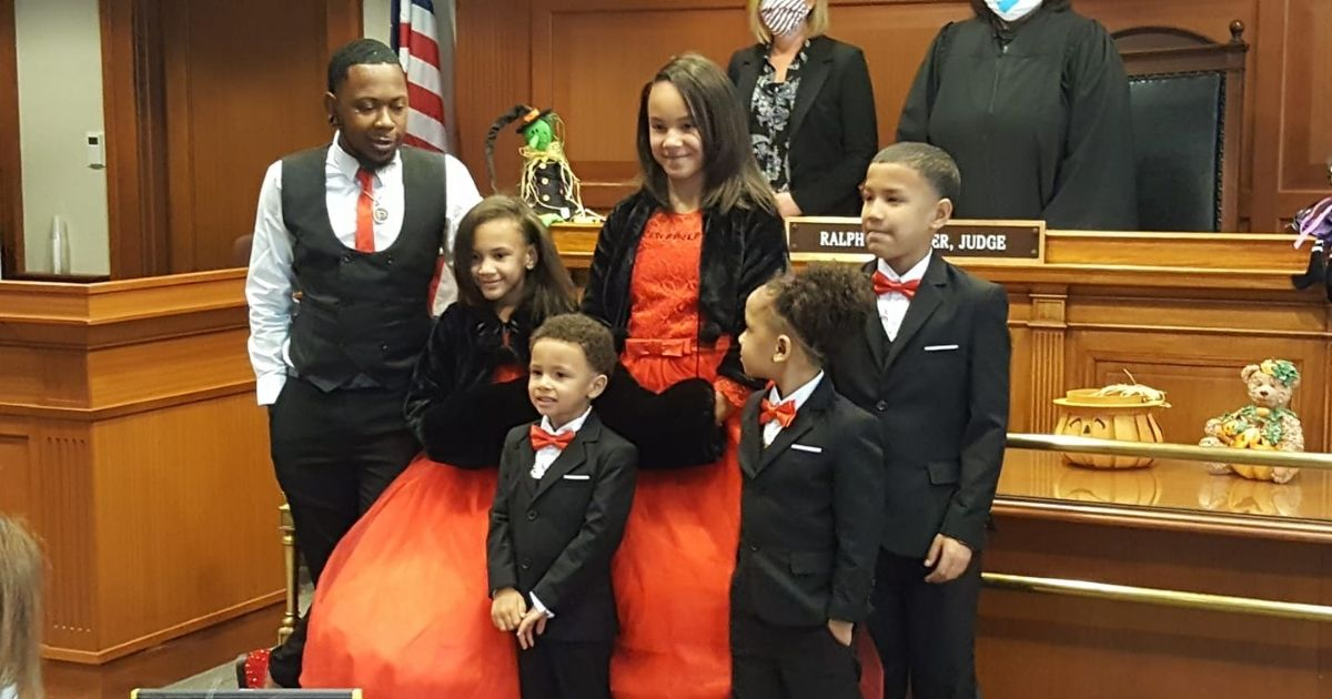 Robert Carter, who went through foster care himself, adopted five siblings on Oct. 30 to keep them together.