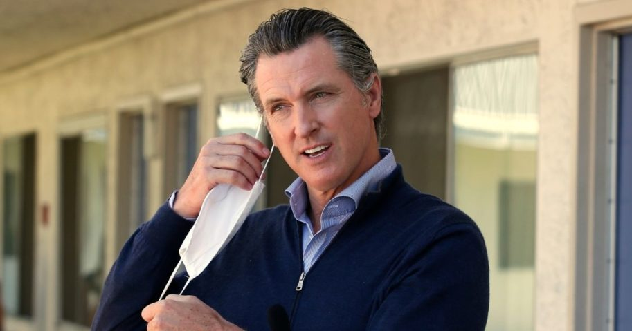 California Gov. Gavin Newsom removes his face mask before giving an update during a visit to Pittsburg, California, on June 20, 2020.