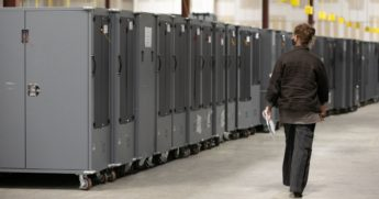 A Georgia Republican Party poll watcher looks over voting machine transporters being stored at the Fulton County Election Preparation Center in Atlanta on Nov. 4.