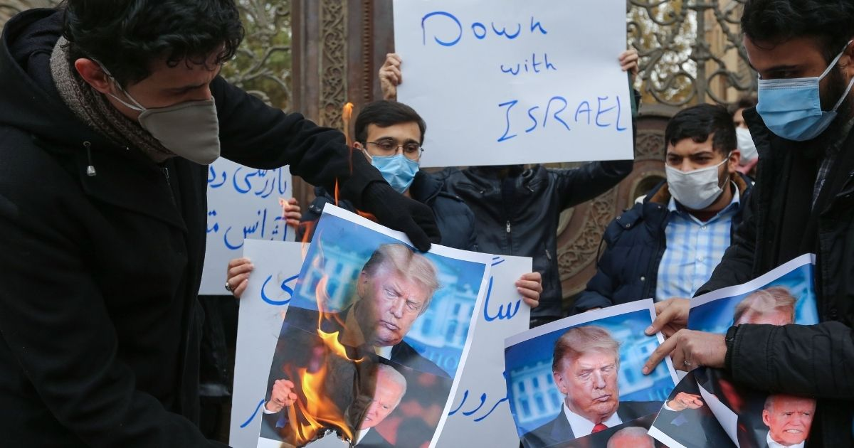 Students of Iran's Basij paramilitary force burn posters depicting U.S. President Donald Trump and presumptive president-elect Joe Biden during a rally in front of the foreign ministry in Tehran on Saturday to protest the killing of prominent nuclear scientist Mohsen Fakhrizadeh a day earlier near the capital.