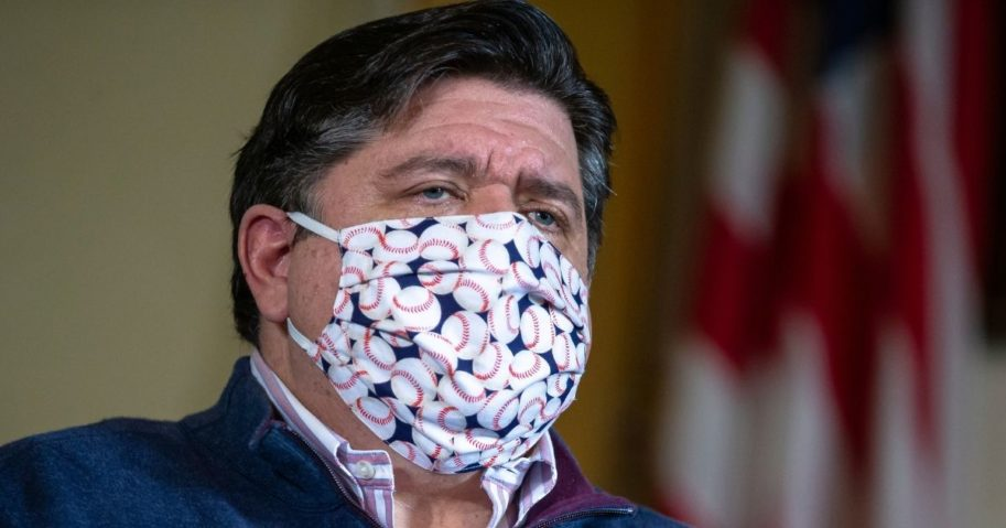 Illinois Gov. J.B. Pritzker wears a face mask made of a fabric with baseballs printed on it during his daily news briefing on the COVID-19 pandemic held in his office at the Illinois State Capitol on May 21, 2020, in Springfield, Illinois.