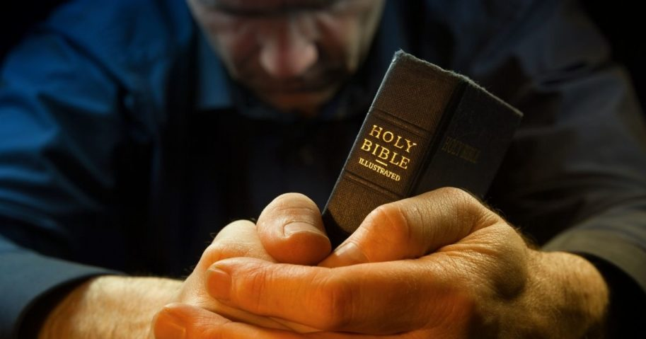 A man prays in the stock image above.