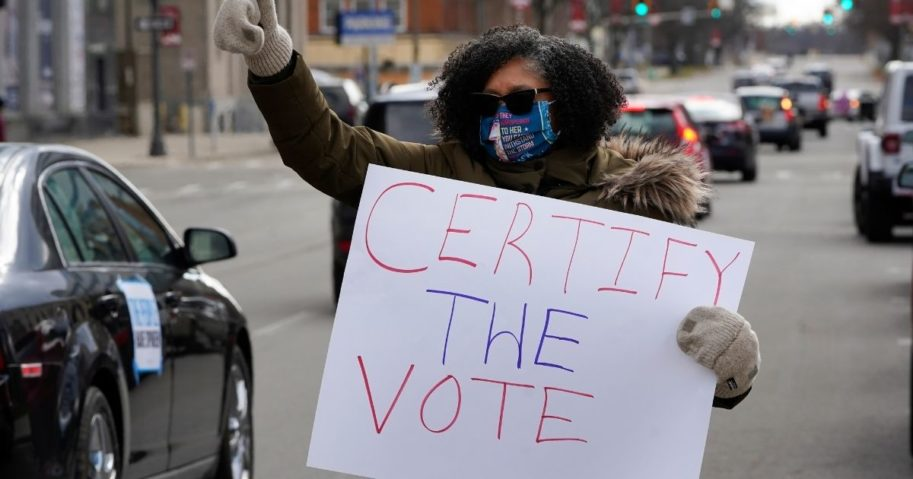 A demonstrator signals to motorists participating in a drive-by rally to certify the presidential election results near the Michigan Capitol in Lansing on Nov. 14, 2020.