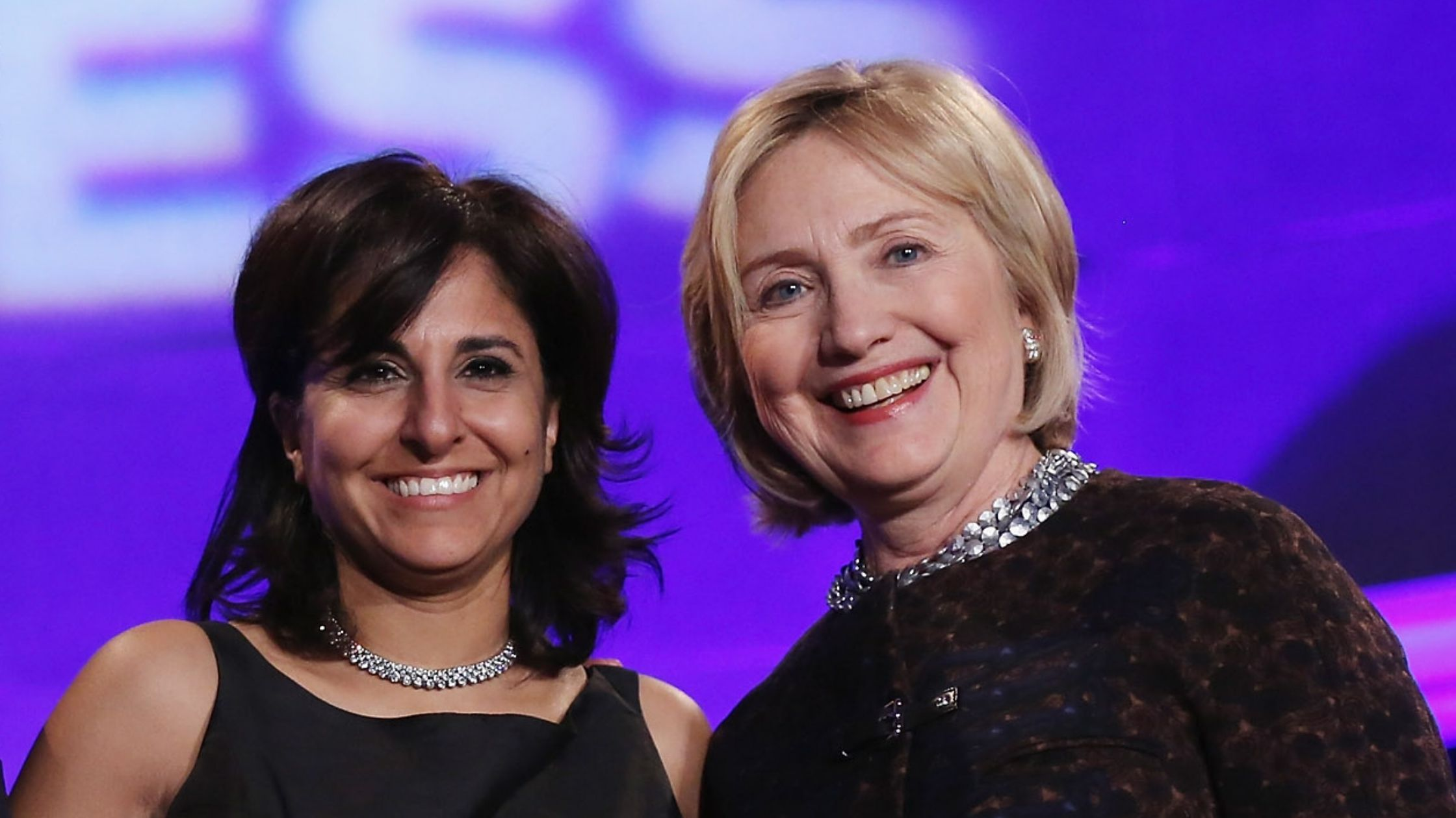Neera Tanden, left, and former Secretary of State Hillary Clinton, right, pose for photographs at the Mellon Auditorium on Oct. 24, 2013 in Washington D.C.