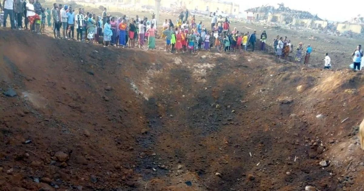 People look into a huge crater resulting from an explosion in Akure, Nigeria.