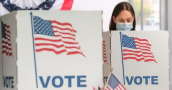 A stock image shows a woman voting.
