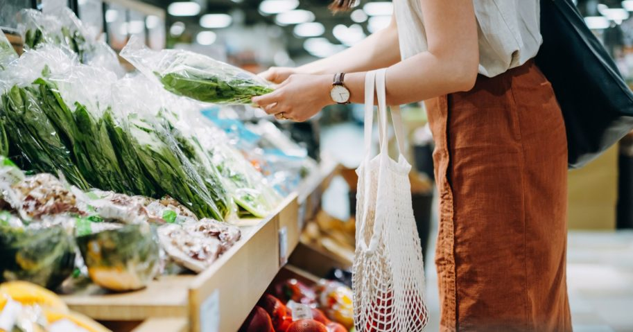 The above stock photo shows a woman shopping for produce at the store.