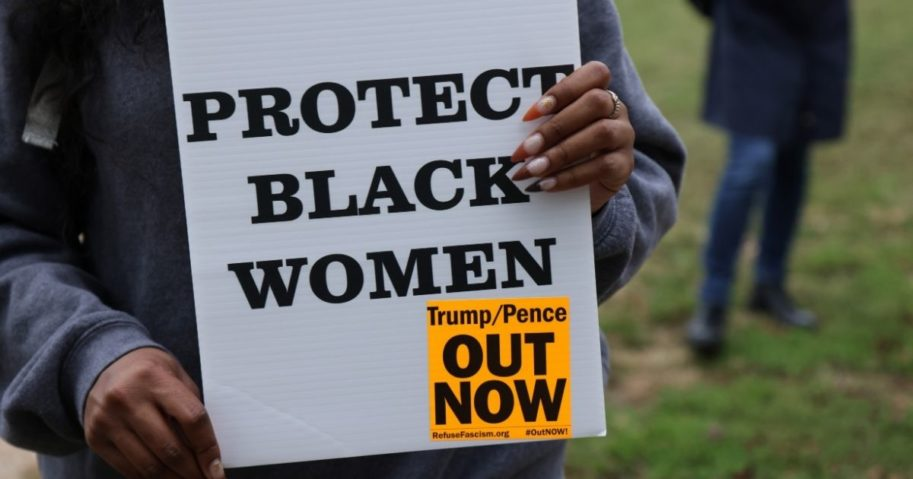 """A woman holds a """"Protect Black Women"""" sign at a rally on Oct. 16, 2020, in Washington, D.C."""