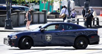 "A Seattle police officer in his patrol car monitors a ""Defund the Police"" march in the city on Aug. 5."