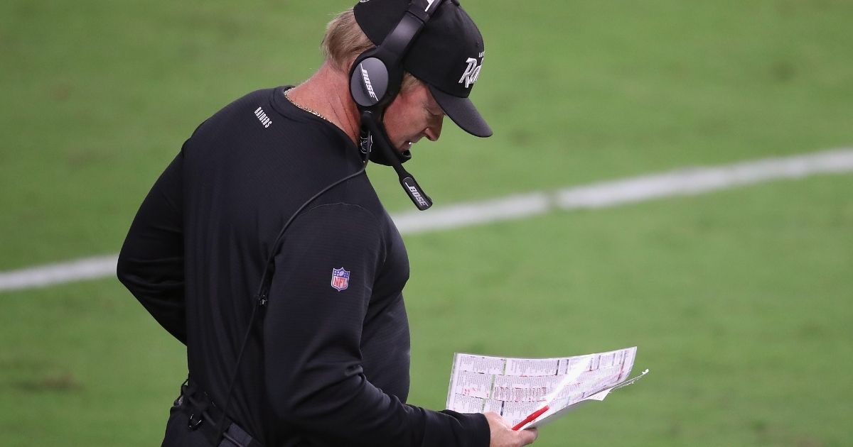 Las Vegas Raiders coach Jon Gruden looks at his play card during the game against the New Orleans Saints on Sept. 21, 2020. The Raiders and Gruden later were fined for the coach going maskless during the matchup, the Raiders' home opener.