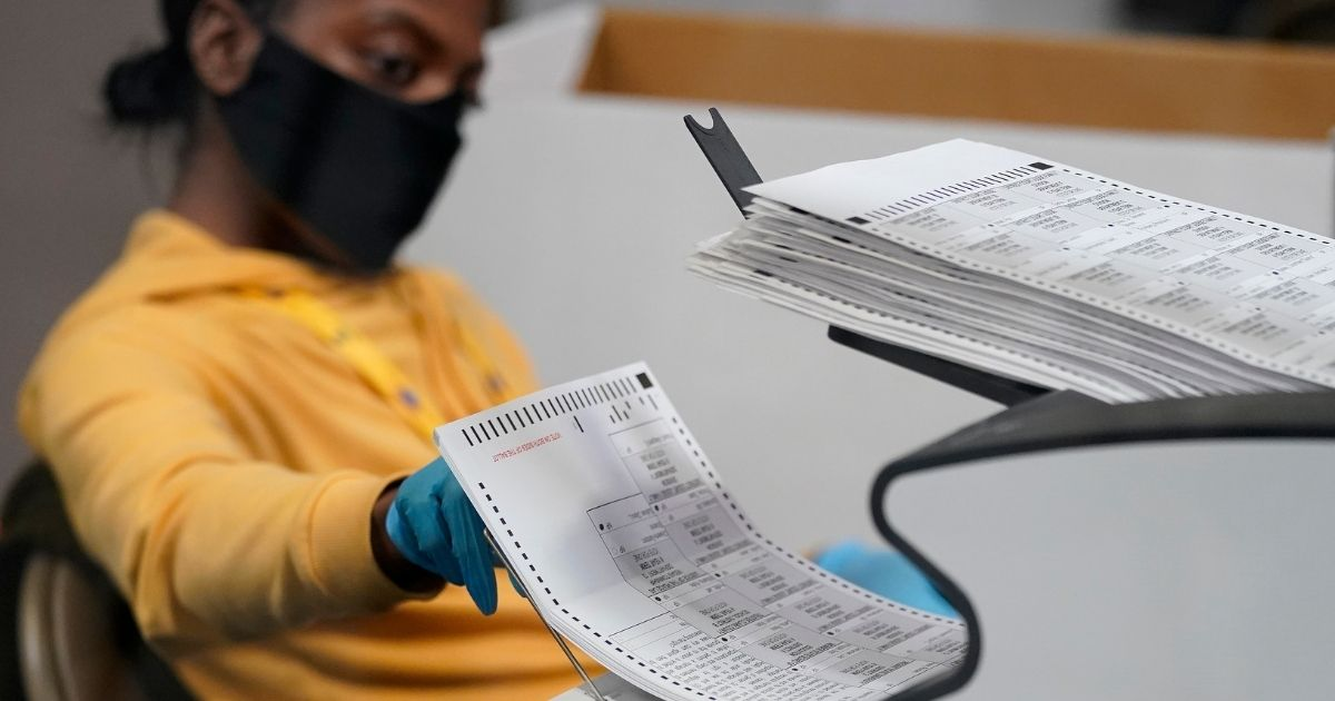 A county election worker scans mail-in ballots at a tabulating area at the Clark County Election Department on Thursday.