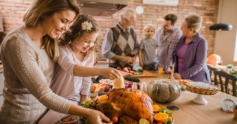 A woman and her daughter prepare a Thanksgiving turkey with family in the background.