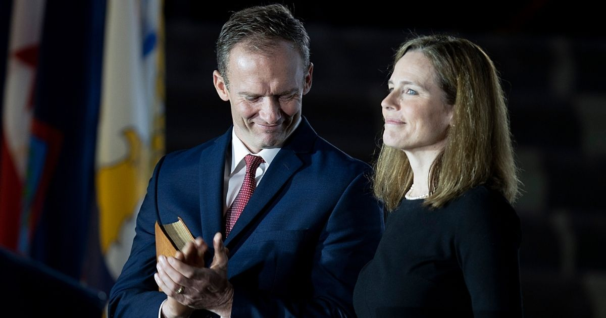 Newly sworn in Supreme Court Justice Amy Coney Barrett and her husband, Jesse Barrett, smile during her ceremony at the White House on Oct. 26, 2020.
