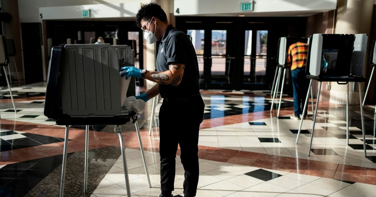 A poll worker sanitizes a voting booth in Denver on Election Day on Nov. 3, 2020. Colorado is one of 15 states that have signed onto the National Popular Vote Interstate Compact.