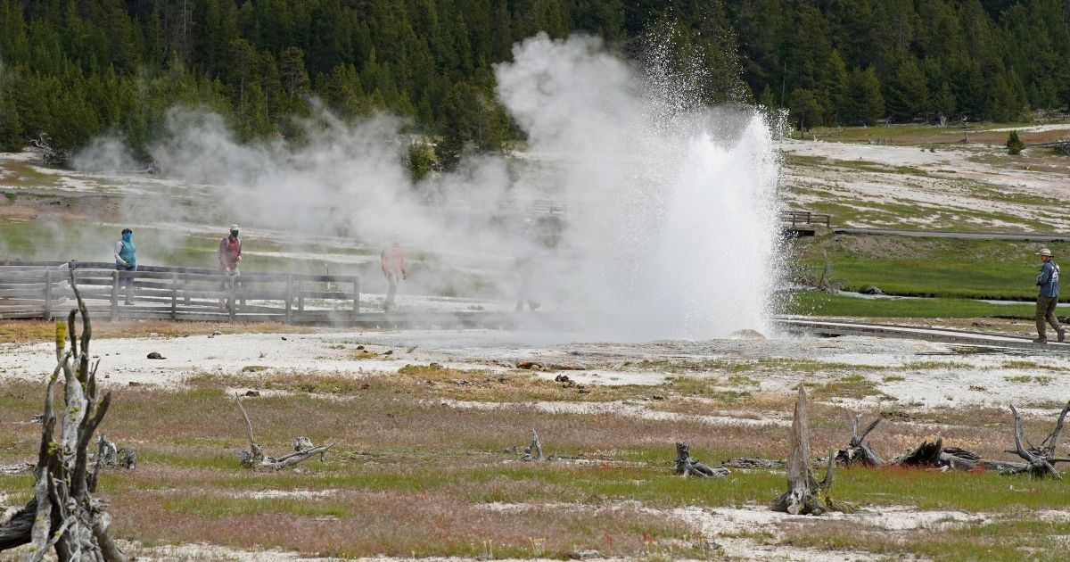 Visitors observe and walk among pools and geysers at Yellowstone National Park outside Jackson, Wyoming, on June 15, 2020. Three men were issued citations, with orders to appear in court, after a fowl incident at the park.