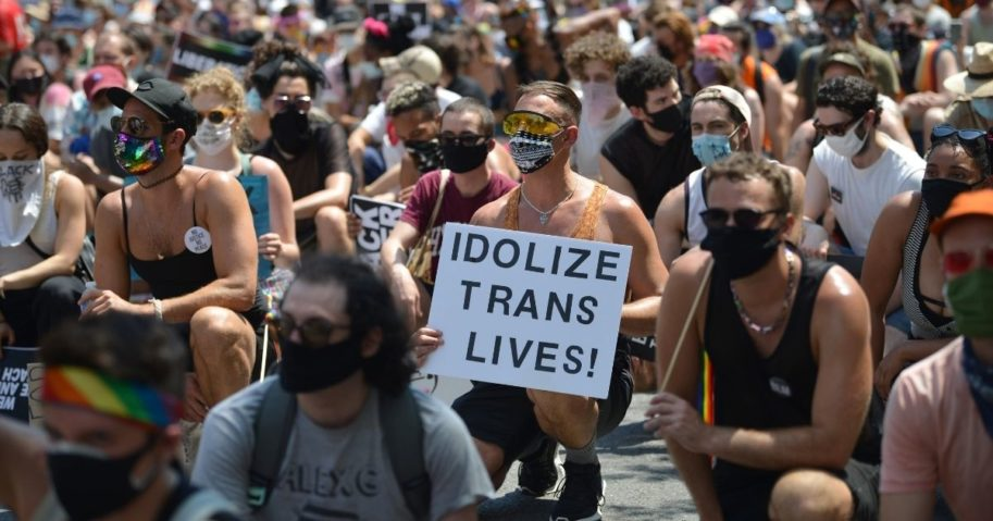 A person taking a knee with others holds an 'Idolize Trans Lives' sign at the Queer Liberation March for Black Lives & Against Police Brutality on June 28, 2020, in New York City.