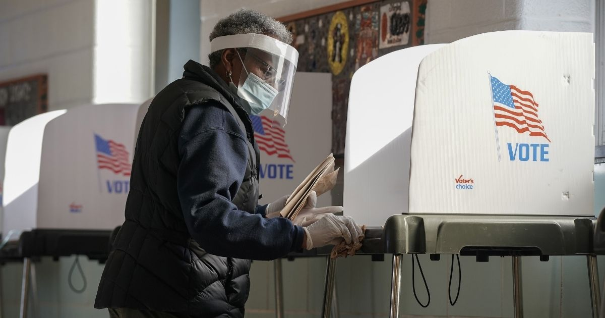 A poll worker cleans a voting booth as residents of Baltimore cast their votes in the U.S. presidential and local congressional elections at Western High School in Baltimore on Tuesday.