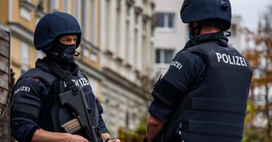 Policemen stand guard in front of a residential building in Linz, Austria, where a man was detained on Nov. 3, 2020, in connection with an Islamist shooting in Vienna the day before.