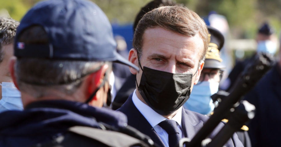 French President Emmanuel Macron speaks with a police officer during a visit to the border between Spain and France at Le Perthus, France, on Nov. 5, 2020.