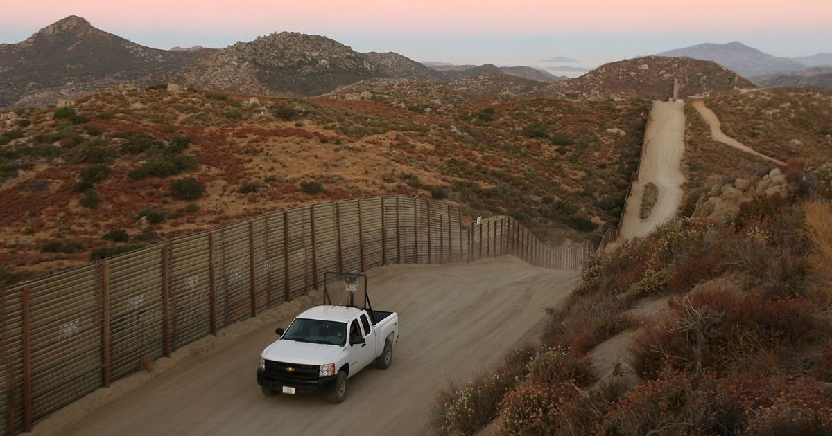 A Border Patrol agent searches for tracks near the US-Mexico border fence on July 30, 2009, near the rural town of Campo, some 60 miles east of San Diego, California.