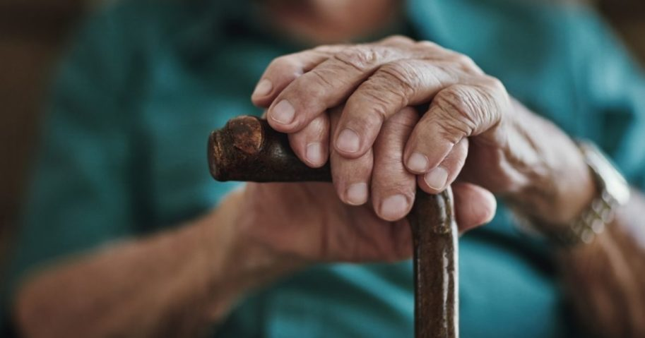 An elderly man holds a cane in this stock image.