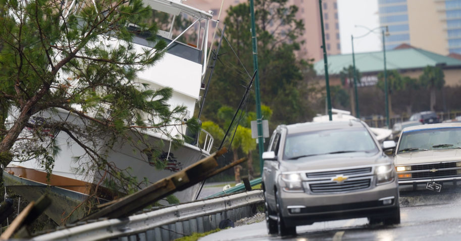 In this Sept. 16, 2020, file photo, vehicles maneuver on a flooded road near a boat washed up after Hurricane Sally in Orange Beach, Alabama.