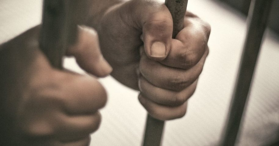 This stock image shows hands gripping prison bars.